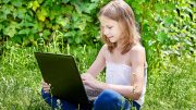 Girl with laptop doing summer homework and reading