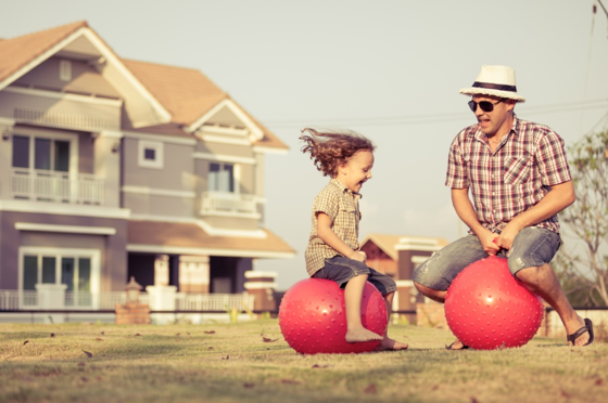 Dad and child bouncing on balls