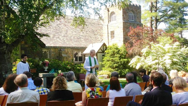 The Rev. Hall Kirkham hosts an outdoor Sunday service in St. Michael's Gardenof Seasons at 112 Randolph Ave. in Milton, MA.