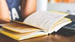 school girl reading notebook classroom