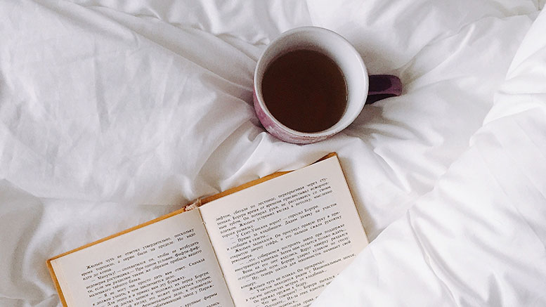 book in bed with tea