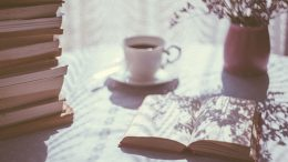 open book with tea and light shining in