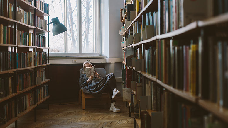 woman in library reading book