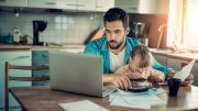 man working on computer with child on lap