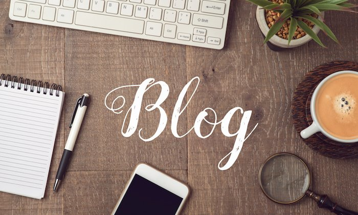The word 'blog' around keyboard, phone, other items