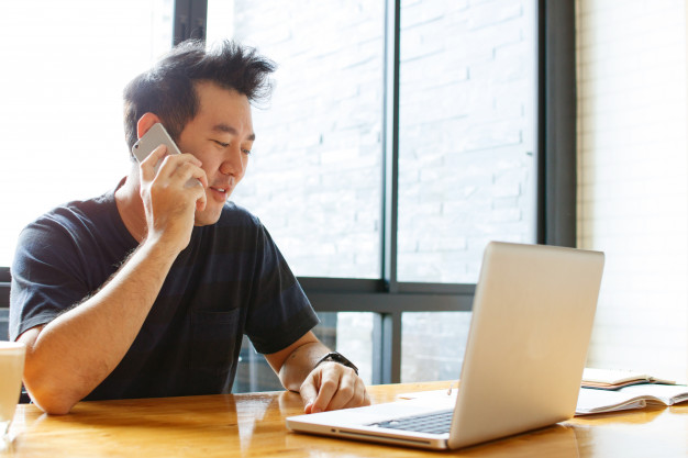 Man on computer and phone